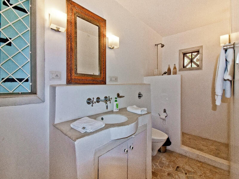 mirror with sink and shower area of villa in candolim on the beach