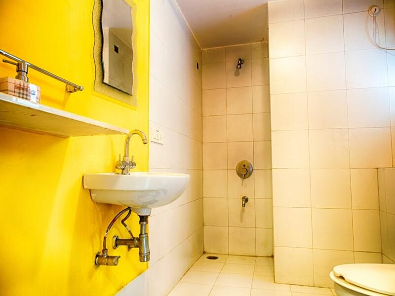 yellow bathroom with shower area and sink